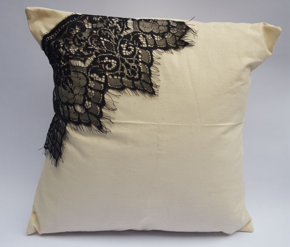 A Natural Calico Cushion with a Black Lace Corner Design