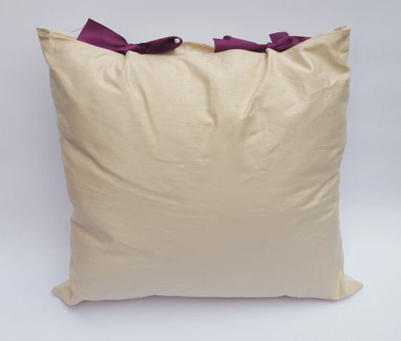 A Handmade Oatmeal like Beige Cushion with a Purple and Green Butterfly Design and Purple Bows