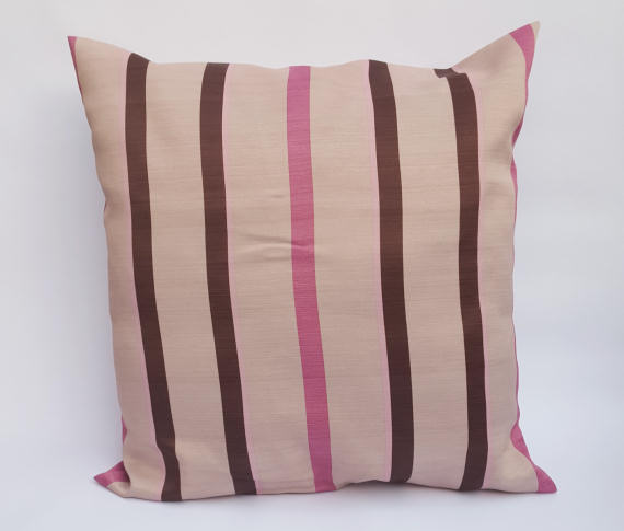 A Handmade Pink and Brown Striped Cushion on Beige.